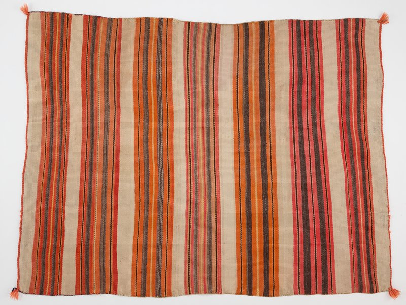 wool panel with cream, red, brown, orange, and yellow stripes, all varying in size; orange fringe in all four corners; thin band of orange threading across top and bottom; brown thread on the two longer sides