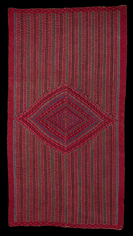 large diamond shape at C with zigzagging stripes inside filled with bright geometric patterns; horizontal zigzagging bands with multi-colored geometric designs in background; intricately decorated borders; overall mauve, blue, black, green palette
