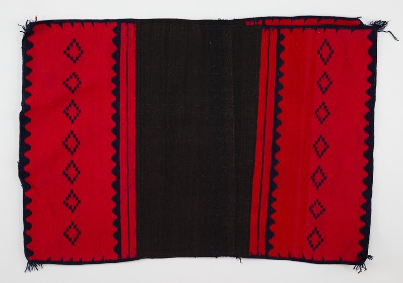 wool dress with red, blue and black dye; dress is connected by loose stitching at the top and on one side in the center with thick, blue thread; blue fringe in all four corners; two bands of red at both top and bottom of both the front and back side with overlaying blue geometric designs; black band of dye in the center of both the front and back side; scalloped edging in blue on the top and bottom red sections with geometric diamond shapes made up of blue squares placed in a line; thin blue lines separate red and black sections