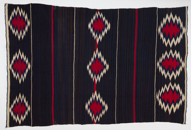three lines of three large red and white ikat shapes; dark background of alternating black and navy blue bands; thinner horizontal red and white stripes