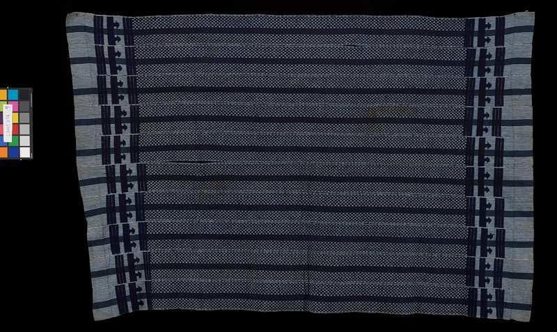 stripes of small blue and white checks; thinner strips of blue checks; wide borders at short ends with white and blue pinstripes; blue embroidery at wide borders with stripes and bars with triangles