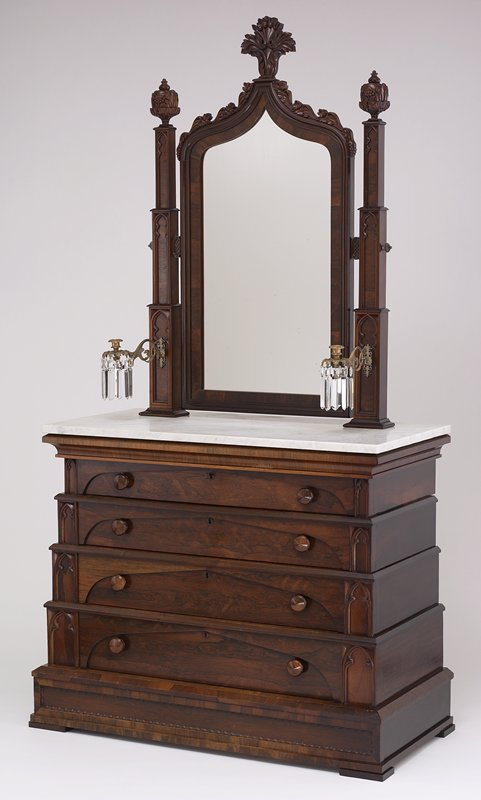 stepped base with four drawers and marble top; two vertical stepped Gothic supports hold mirror; each mirror support has brass candle sconce with ten crystal pendants