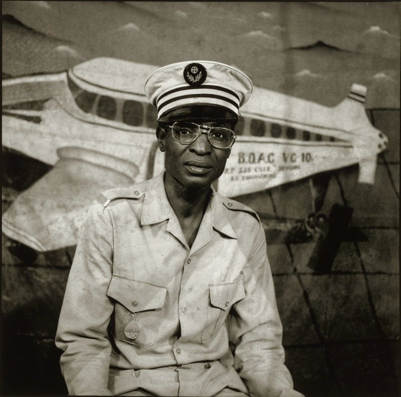 portrait of a black man wearing a simple military uniform with a flat-topped hat and with a medal on his PR breast pocket; picture of a plane behind man