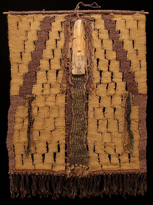 wall hanging; openwork weaving in thick strands of tan and brown; vertical wood element at top center; central vertical strip below wood element in green-grey and brown; shorter vertical elements with twisted tassels in brown, green, grey and tan; thick brown fringe at bottom