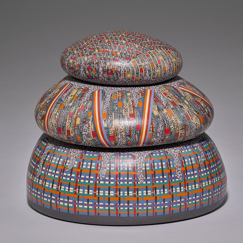 stacked vessel with three layers; each layer intricately painted; bottom layer has basket-weave pattern with bright colors; center and top levels have tiny bars with geometric designs separated by bead-like forms of bright colors; squiggle patterns in drip-form at top of lower layers; top layer has two segments of contrasting striping