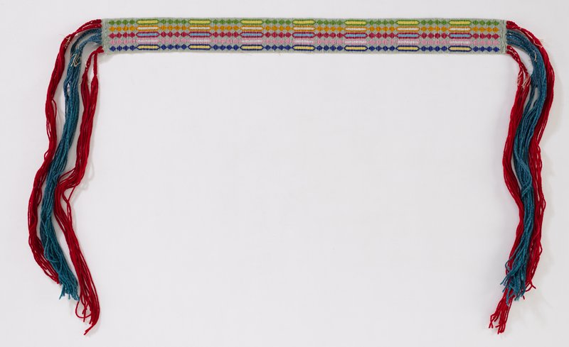 central loom woven beadwork section with 'otter tail' design in blue, yellow, pink, white and green beads on grey beaded ground; 2 pairs of red yarn tassels surrounding 4 blue yarn tassels on each end
