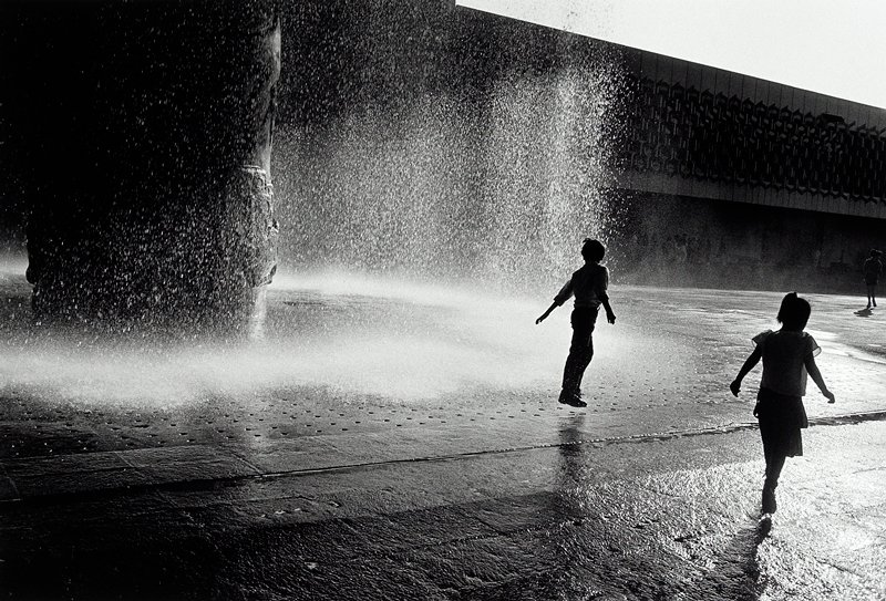 boy and girl with backs to camera in paved square; large fountain in left 3/4 of image; boy is jumping in water