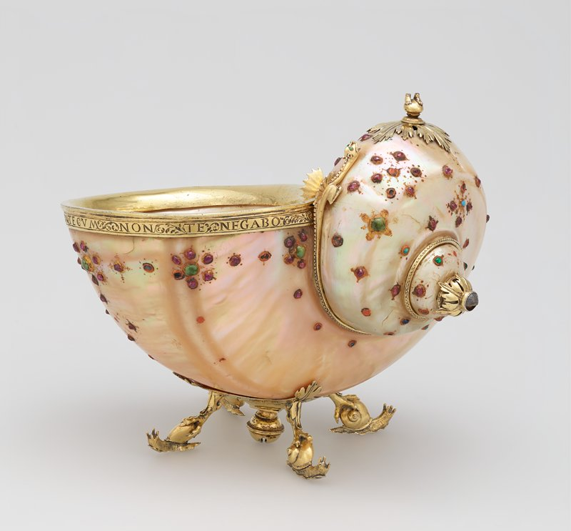 large pearly iridescent shell fashioned into a cup; gold edging around opening with text and leafy design; dragon with wings and green eyes at front of raised portion of shell; leafy element in gold at top of raised portion with feet only remaining on top of ball; four feet in the form of snails; bell-like form at center bottom between feet; floral-like designs in red and green stones on body of shell