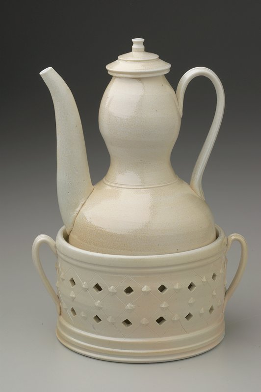 cream glaze; round bodied ewer, circular bowl with square walls and open-work design; banding at rim and foot of bowl and ribbed ribbon handles at either side