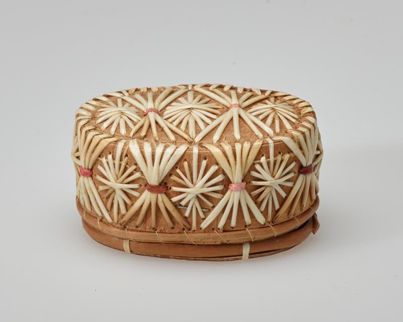 small oval box; flat top and bottom; top and edges of cover decorated with starburst and X designs in white, pink and red quills