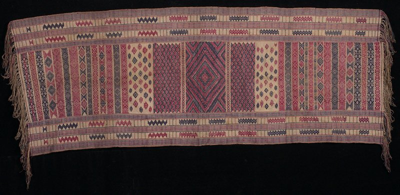 3 strips (2 narrow flanking a wide strip) sewn together; tan ground with geometric (primarily zigzag and diamond) supplementary weft patterning in red and blue; tan, red and blue twisted fringe on each short side. Woven fabric