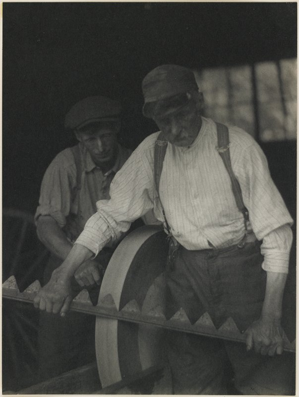 middle-aged man with mustache holding a saw-toothed metal bar to a grinding wheel attended by a younger man at L; both men wear caps, shirts and pants with suspenders