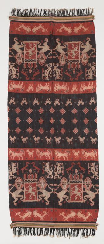 ikat; rust red, brown, blue, white; two panels sewn together vertically; symmetrical designs, top and bottom; alternating rows of brown and rust; rust colored rows have horses alternating with roosters, or pairs of facing fish; wide brown rows have pair of rampant lions flanking a crowned horse on a crowned shield, with pair of rearing horses (?) and pair of walking birds; central brown field with white and rust red diamonds and rows of roosters in white; received with attached Velcro heading band