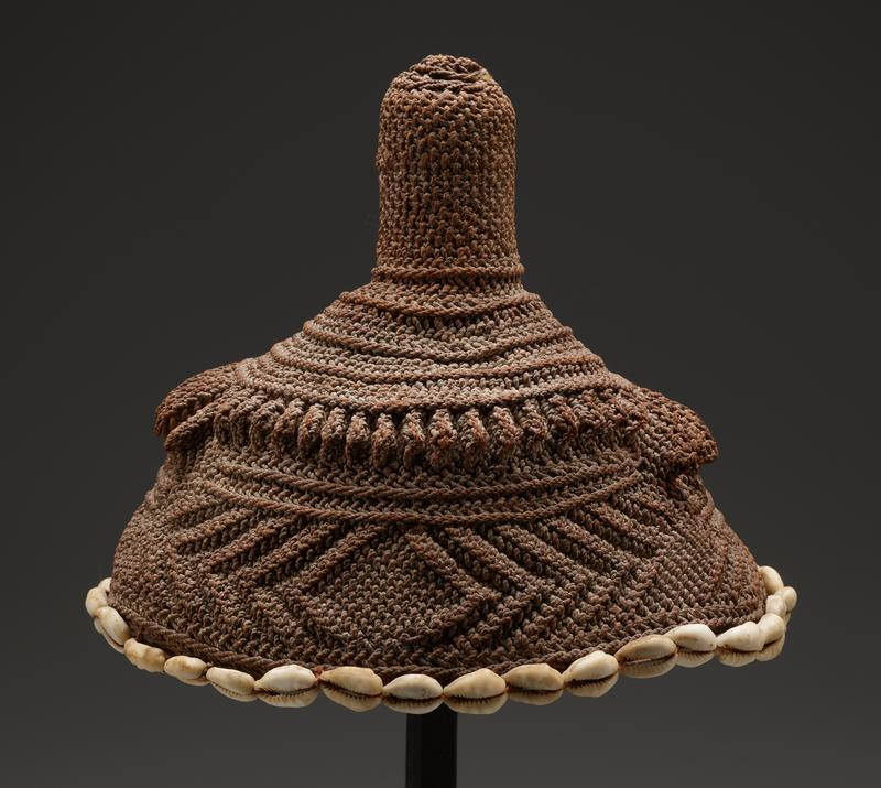 beanie with vertical knob on top, reinforce with plug of wood at interior; beige crocheted threads with bands including diagonal lines and raised triangular wedges in two different sizes; band of cowrie shells at bottom edge