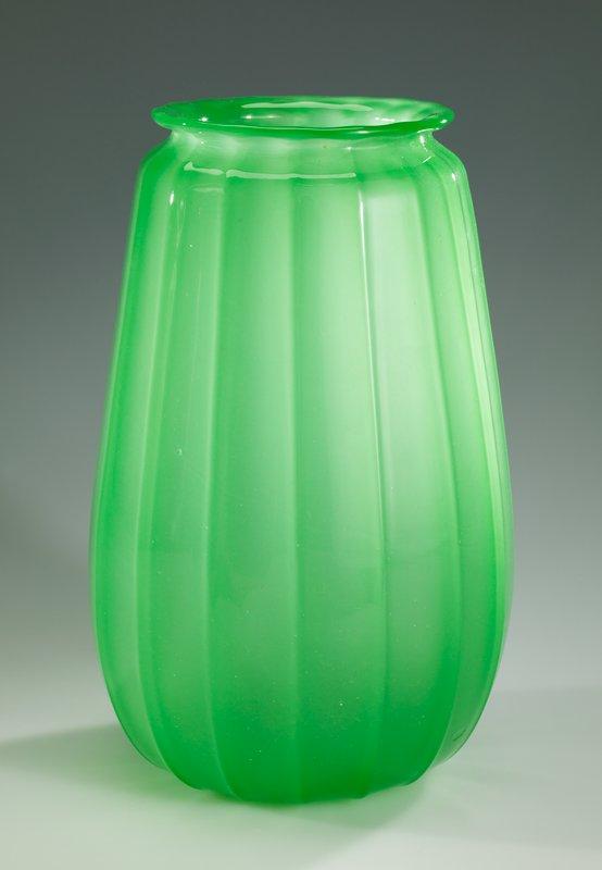 Bulbous, slightly tapering form; exterior fluting; outward-turned lip; jade green