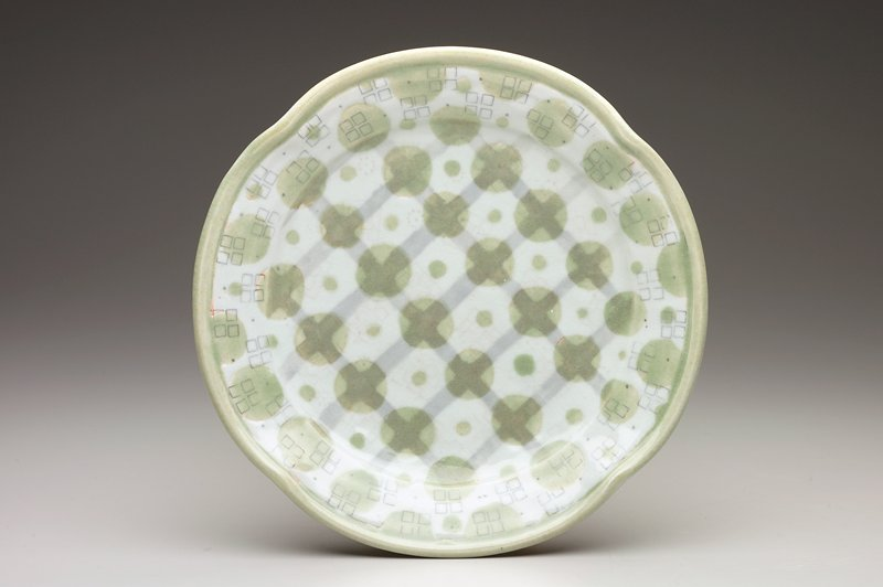 plate with 4 ridges in rim; heavily decorated on both sides with groups of 4 squares, green dots in 2 sizes and grey grid on top, tan grid on bottom