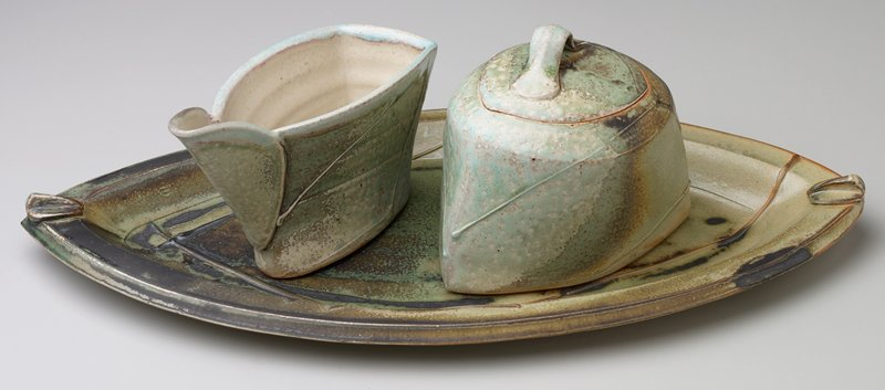 rounded wedge or boat-shaped bowl; small cover with applied loop handle; linear elements on body; aqua, green and tan glaze with cream interior