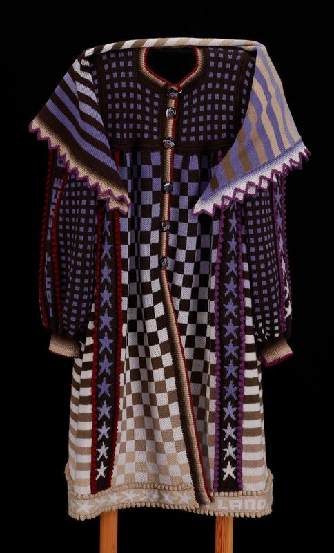 "knit coat and scarf; bright and dark purple, black, brown, maroon, and tan; coat: checker ombre panels on front and back; black shoulder pad linings; pocket at each side; striped side panels; black chest and sleeves with purple squares; bands of purple ombre stars on front, back and sleeves; bobbles border bands of stars and buttons; black square buttons with flowers on upper body and ends of sleeves; proper right sleeve has band reading, ""Don't fence me in / Give me land, lots of land under starry skies above"" scarf: square, striped purple, brown, black, tan, stripe with scalloped edge"