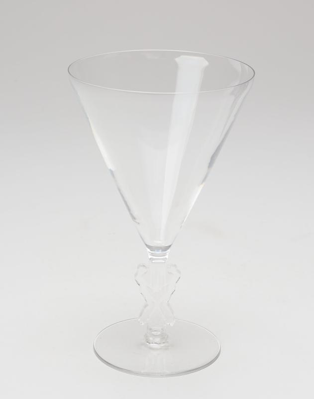 Conical glass; stem is 2 figures facing each other, knees bent, holding hands; flat foot; clear glass