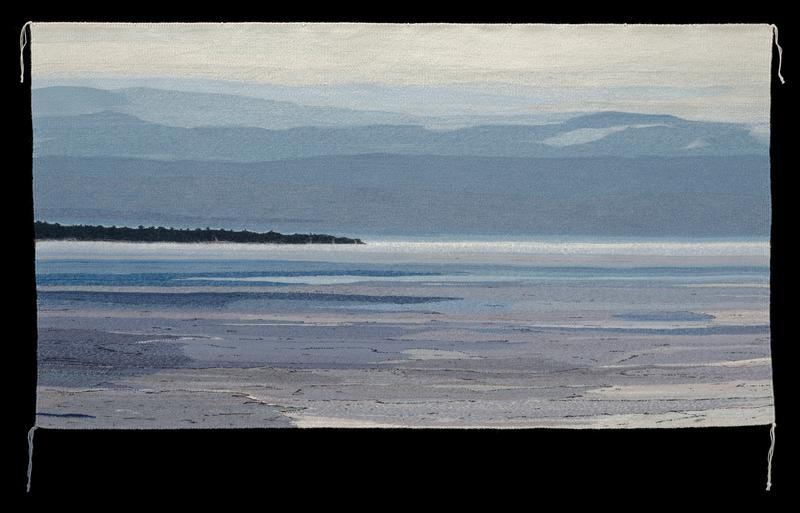 landscape/waterscape in series of blue and greys; thin island at left, middle ground in dark blue; mist on water's edge in white, longer yarn; tassel of three tied threads at all four corners