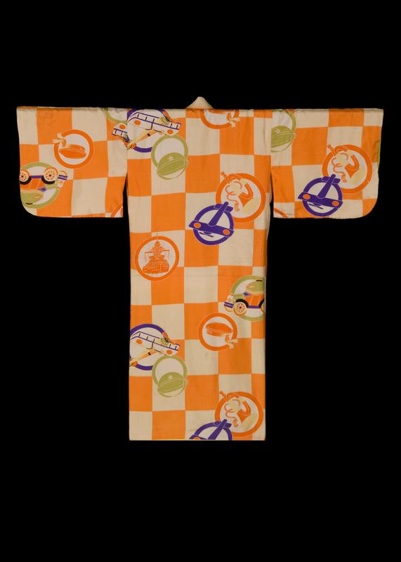 child's kimono with orange and white checkered pattern, with colorful, circular repeating patterns of toys such as airplanes, trucks and ships