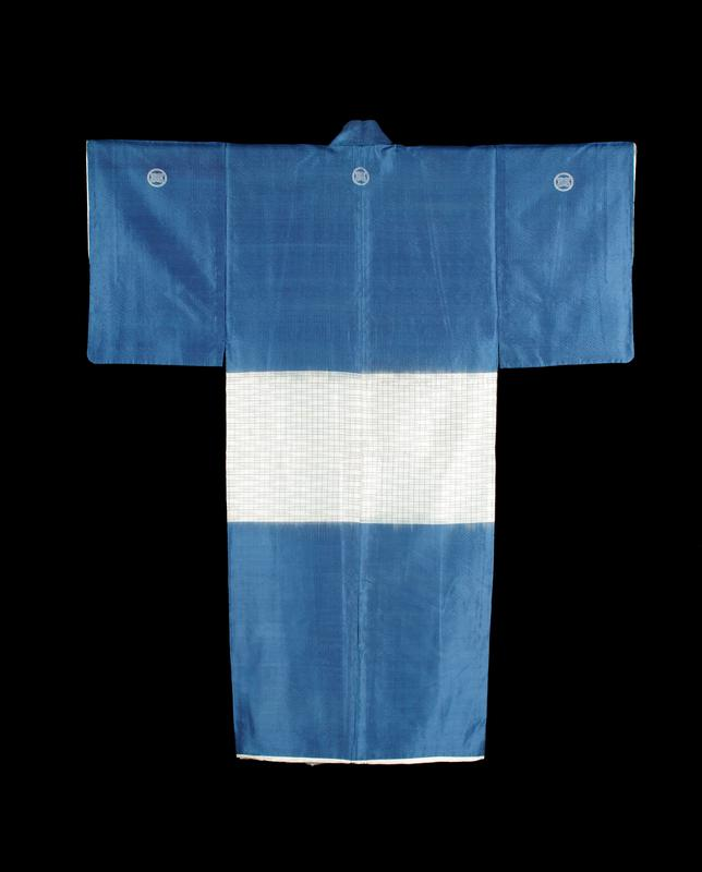 blue silk kimono, with band of white with linear repeating pattern in center; two embroidered emblems on PR and PL chest area, as well as on back PR, C and PL sleeves