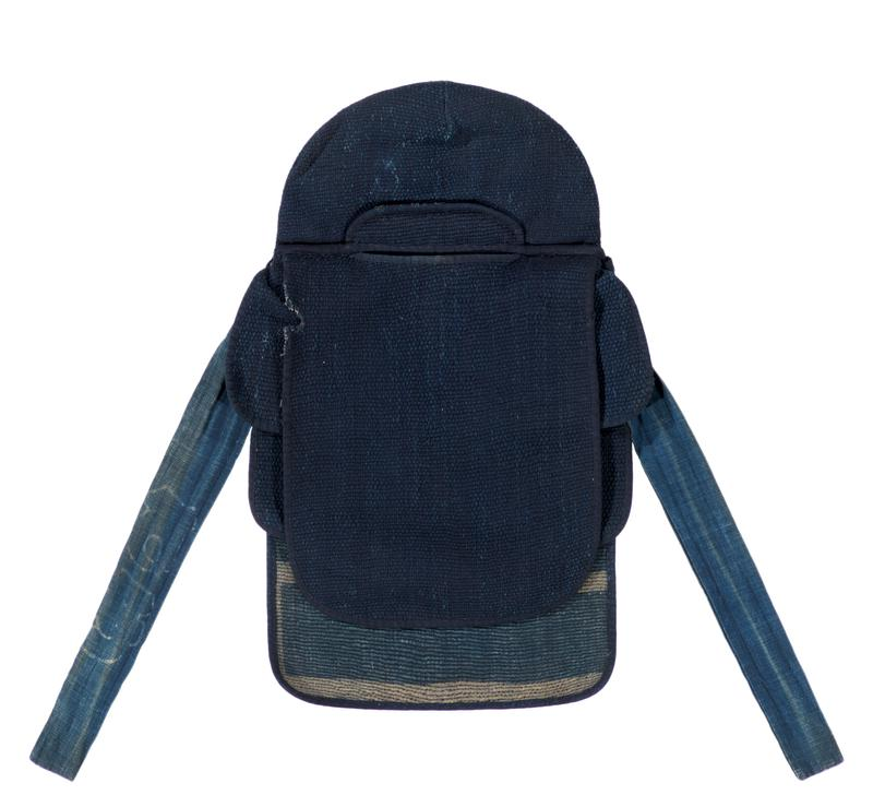 navy blue, tihgtly knit hood with front and back covers; slit in front with small bill above; two flaps and a fabric tie on each side, with a button on each R flap; blue interior with off-white horizontal and vertical line design