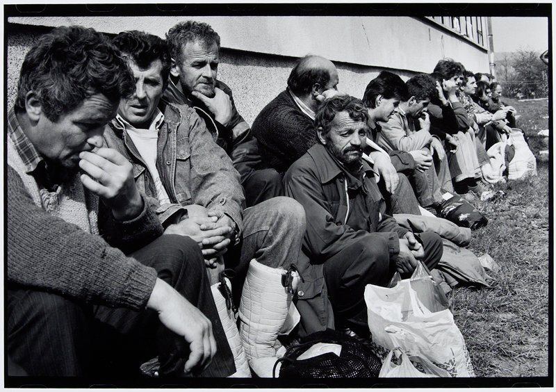 row of men seated in grass along building wall