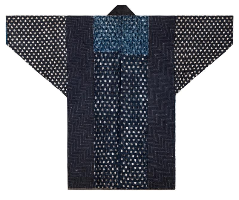blue and black coat with various patterned fabrics; black collar with gray lower lapels; black sleeves with white pattern, navy shoulders with stepped blue stitching, patterned blue chest with stepped embroidery along lower 2/3 and light blue diamond embroidery that continues to verso, solid blue lower section with stepped stritching; light blue lining on back interior; white lining on front interior sections with Japanese characters printed in black on PR and a large blue flower printed on PL; white PL sleeve interior lining with black print; verso has dark navy side panels, solid blue center panel with white pattern, stepped embroidery over all sections with light blue diamond embroidery only over TC