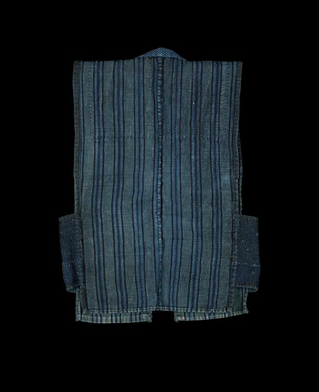 blue vest with dark blue, medium blue, and gray-blue vertical stripes; dark blue fabric with yellow stripes appliqued to lapel; patches of dark blue fabric with yellow plaid appliqued to shoulders and yolk; embroidered side panels