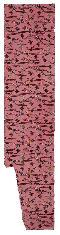 rectangular fragment of pink fabric with section cut out of LL; pattern of black vines and birds, with multicolored flower blossoms (blue, red, yellow, and purple) and green birds scattered throughout