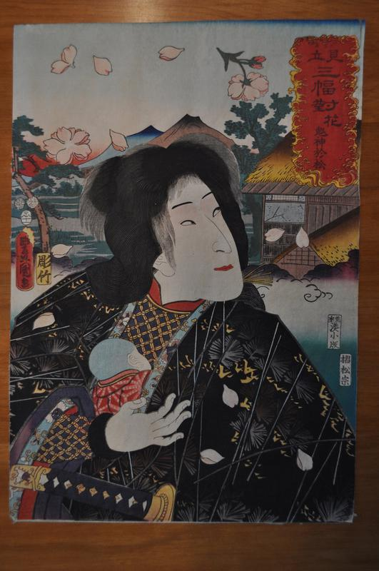 woman in black patterned kimono looking over her PL shoulder, holding a baby to her chest