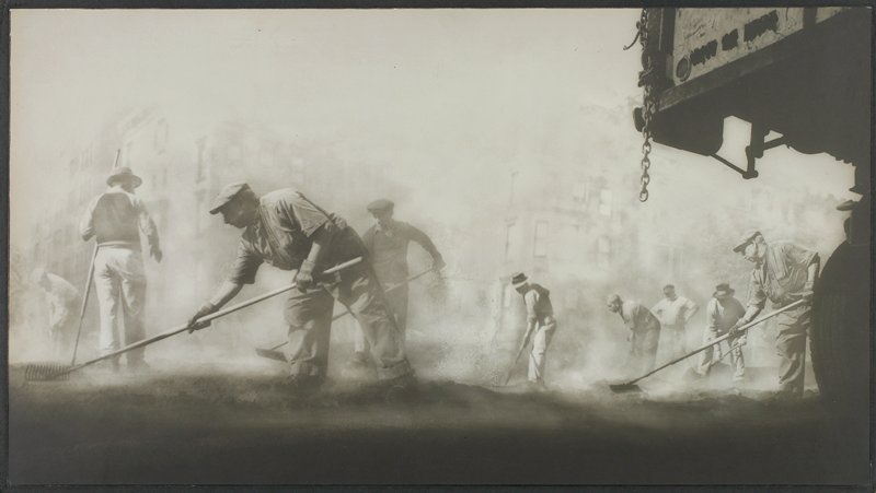 nine men raking steaming pavement in front of large buildings, seen through fog; truck bed and wheel at R edge