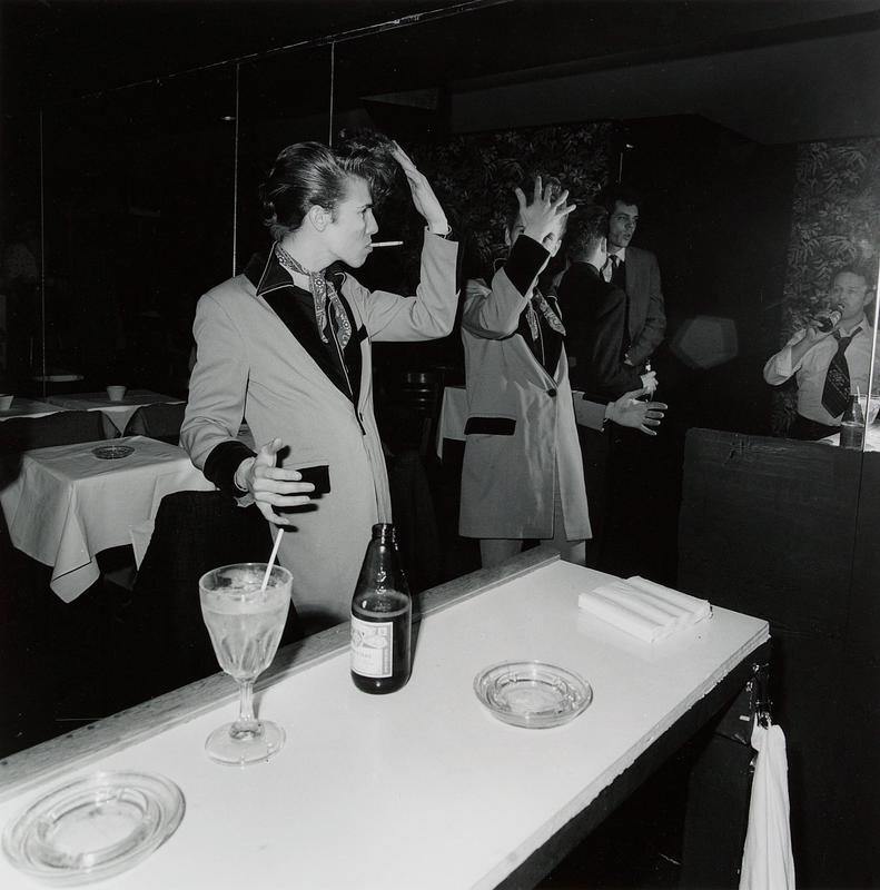 young man in jacket with velvet lapels and cuffs and bandana tied around his neck, smoking a cigarette and touching the front of his pompadour hairstyle with his PL hand; 3 other figures reflected in mirror at right; bar at front of image