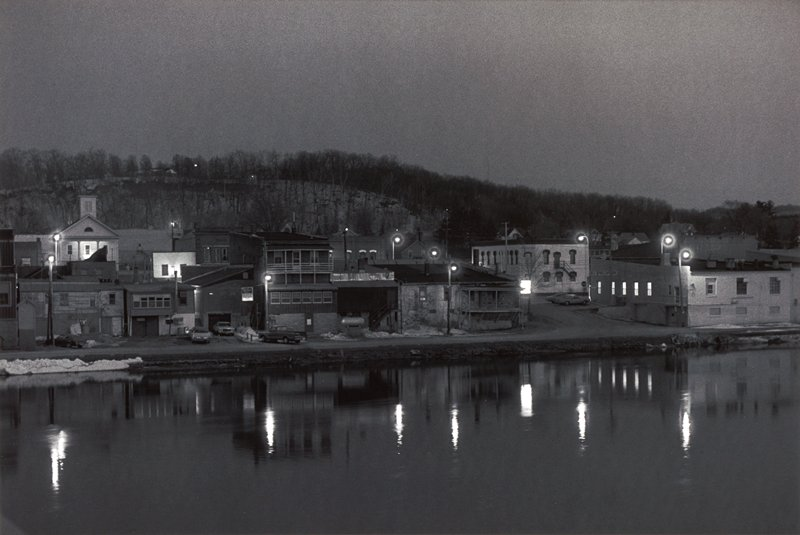 riverside town at dusk with lights and buildngs reflected on the water