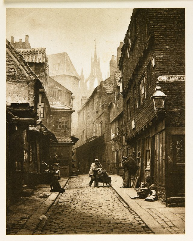 narrow, dark, brick street with tall building on both sides; shadowy castle towers visible in background; women and children standing and seated on sidewalk with man at center seated on wheelbarrow handle, from a portfolio with essay on the photographer