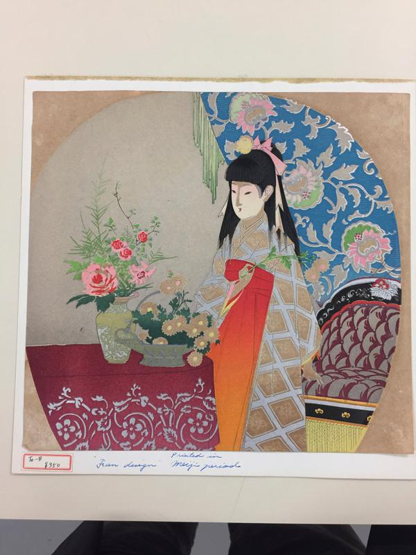young girl wearing kimono with orange skirt and silver and tan checked top arranging flowers in a basket and vase