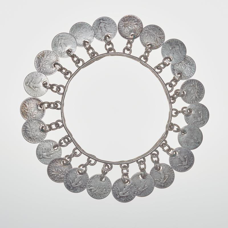 circular bangle with 22 coins, each attached by two circular chain links to a piece of twist wire at middle of bracelet; coins are French 50 centimes pieces with a figure surrounded by text on one side and a branch of leaves with text on the other