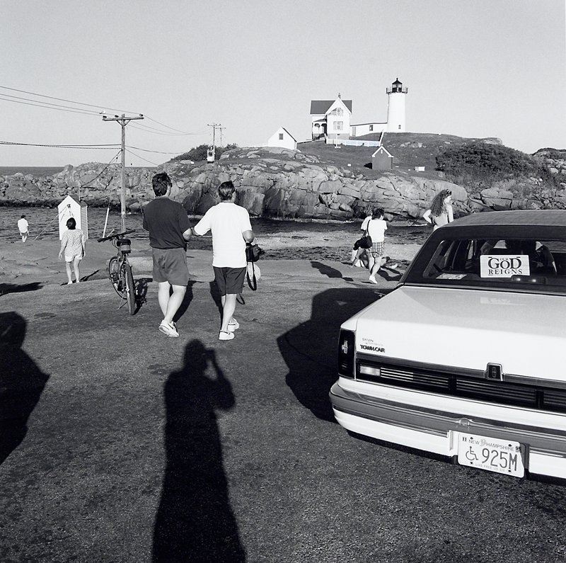 lighthouse and small house at top of hill, URQ; 2 men in shorts at center walking toward lighthouse, with other figures in front of water at right and left; car at right; photographer's shadow visible in LLQ