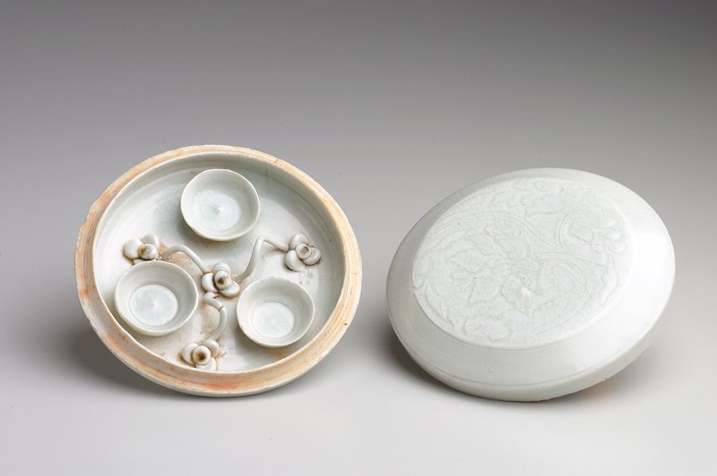 circular, flat box on a low foot ring; light blue glaze; cover decorated with lightly incised floral decoration; box contains 3 small attached bowls with 4 floral shapes connected with vines (all made from clay) attached to bottom