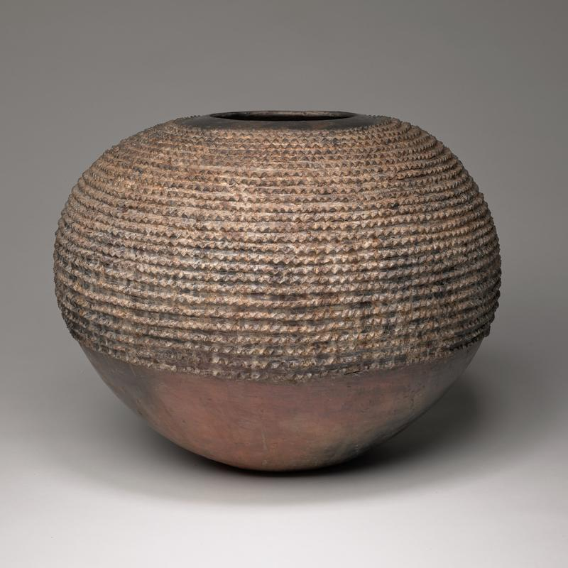 rounded pot with tapered bottom; hole at top with smooth border; upper section is textured by rows of small pyramid shapes; bottom section is untextured