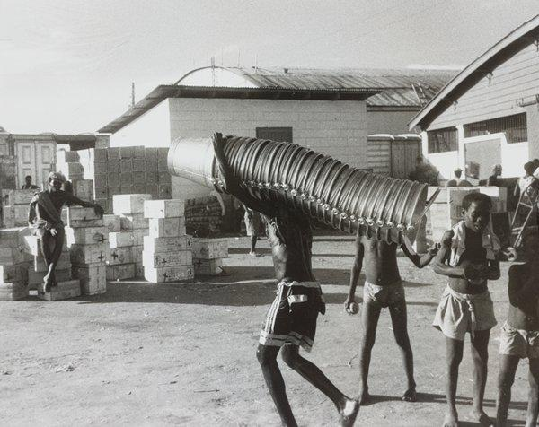 Black and white photograph of man carrying a stack of buckets in an exterior scene