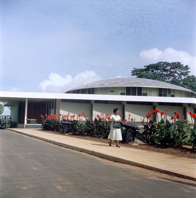 Color photograph of a woman walking down a sidewalk in front of a building with a domed room and red flowers