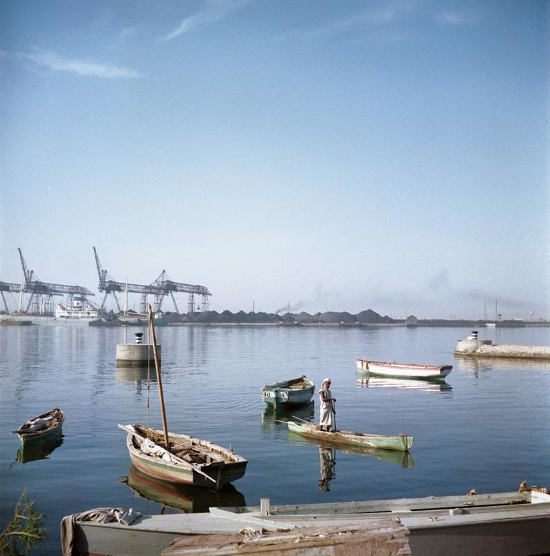 Color photograph of a body of water with boats and a figure in the foreground and industrial work happening on the background