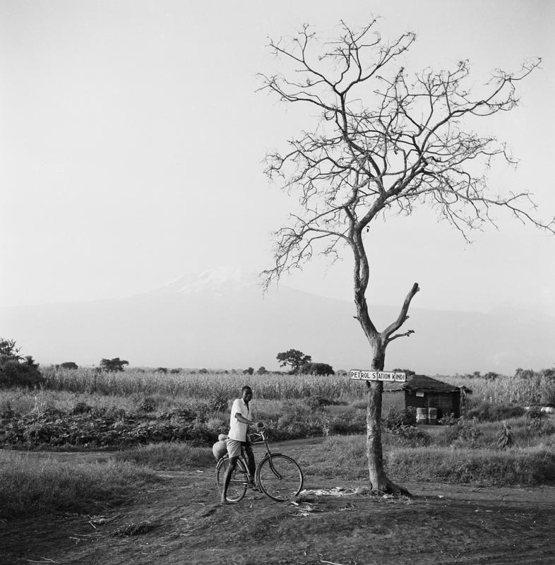 """Black and white image of a man on a bike under a tree with a sign on it that says """"Petrol Station Kindi"""""""