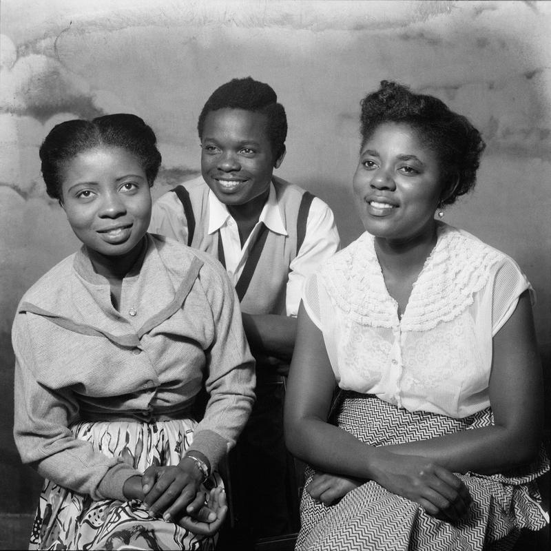 Black and white photo of three smiling, seated figures with their hands in their laps