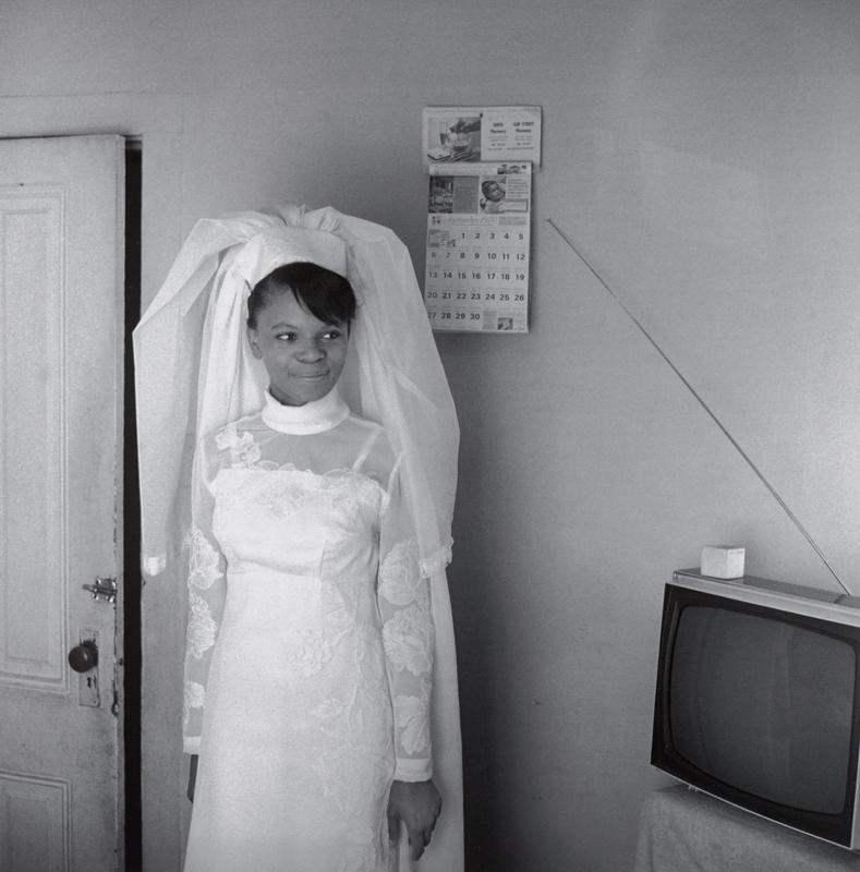 black and white image of a smiling Black woman wearing a long-sleeved wedding gown and a headpiece with a veil in front of a wall with a door at left, calendar at right and TV in LRC
