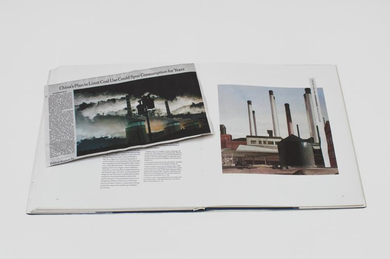 color image of a newspaper clipping with a photomontage of smokestacks on top of a book with the reproduction of a Scheeler painting of smokestacks