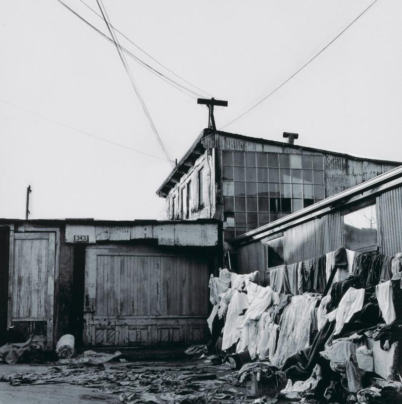 black and white image of dilapidated buildings of wood and corrugated metal, with grid of windowpanes at top center; piles of clothing and other textiles draped up at right and strewn on ground in foreground; electrical wires forming V at top of image