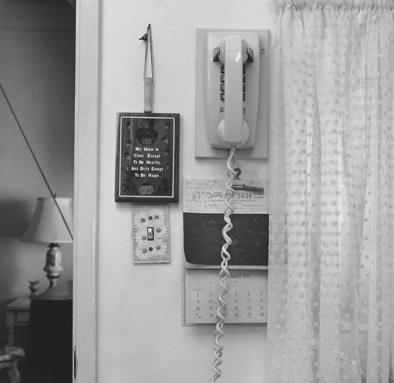 "black and white image of a push-button wall telephone with a calendar hanging below it; plaque to left with text: ""My House Is Clean Enough To be Healthy, And Dirty Enough To Be Happy""; light switch with daisy motif switch plate below; polka dotted curtain to right"